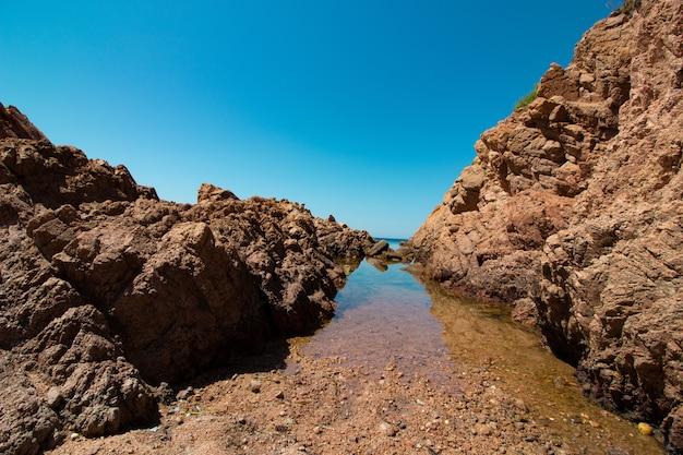 Landschap dat van grote rotsen in een open zee met een duidelijke zonnige blauwe hemel is ontsproten
