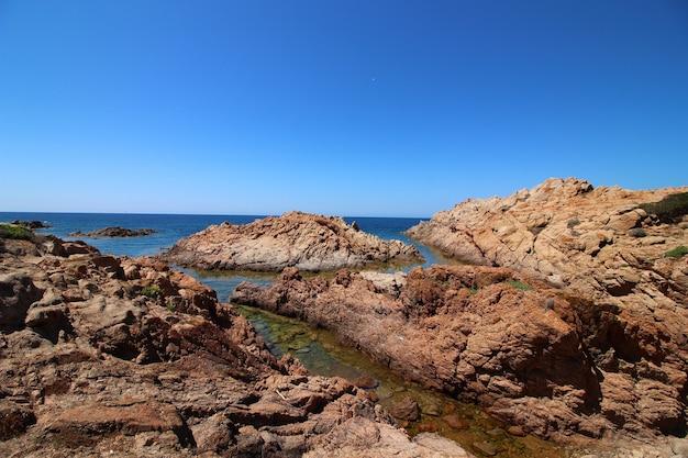 Landschap dat van kust met grote rotsen in een duidelijke blauwe hemel is ontsproten