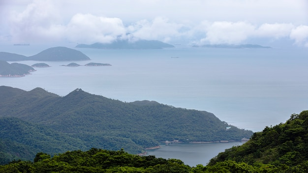 Landschap en zeegezichtberg en het overzees en verschepende ladingscontainers in het regenseizoen