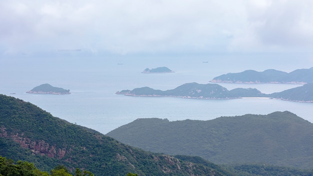 Landschap en zeegezichtberg en het overzees en verschepende ladingscontainers