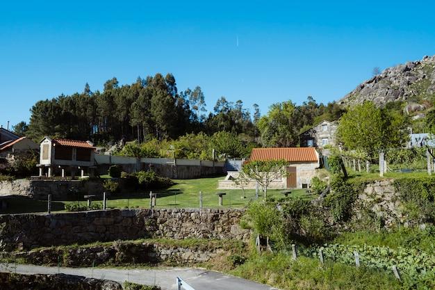 Landschap in het noorden van spanje, de landelijke regio van galicië. landschap platteland in de zomer. natuur, reizen en vakanties concept. panoramisch uitzicht op het prachtige groene uitzicht op kleine spaanse dorp.