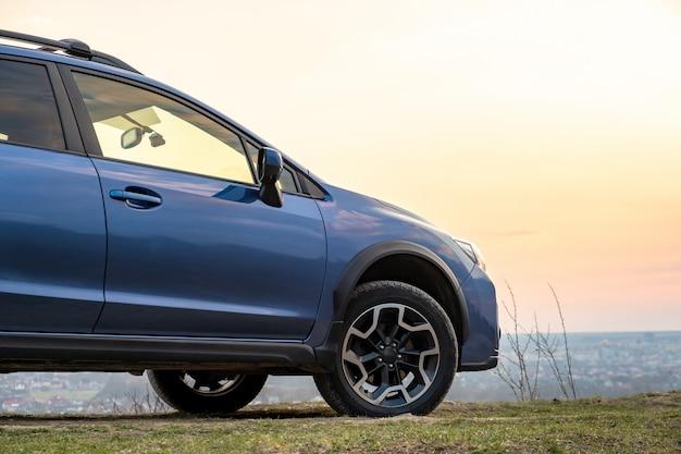 Landschap met blauwe off-road auto bij zonsondergang, reizen met de auto, avontuur in de natuur, expeditie of extreme reizen op een suv-auto.