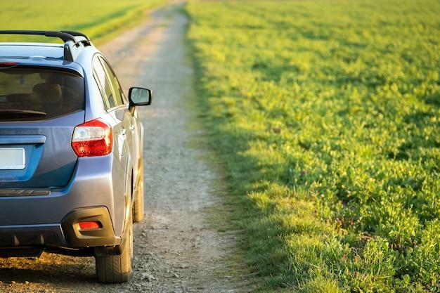 Landschap met blauwe off-road auto op onverharde weg
