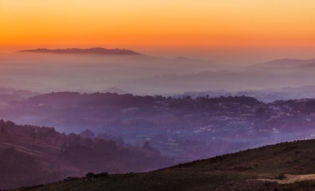 Landschap met de zonsonderganghemel boven lagen mistige bergen