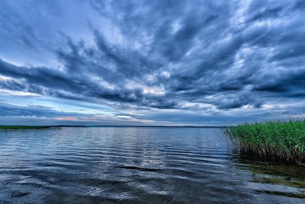 Landschap met een avondmeer en een dramatische lucht