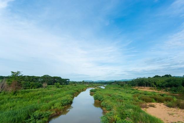 Landschap met grasachtig gebied, rivier klein in de avond.