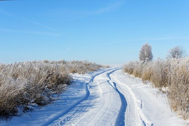 Landschap met landweg in zonnige winterdag.