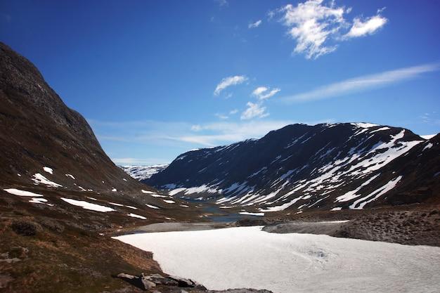 Landschap met meer en bergen bedekt met sneeuw in noorwegen.