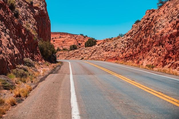Landschap met rotsen, blauwe lucht met asfaltweg in de avond.