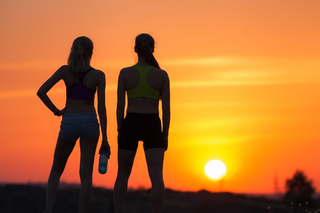 Landschap met silhouet van jonge sportieve meisjes bij zonsondergang