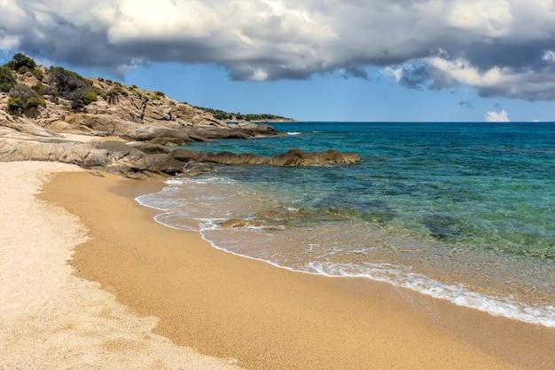 Landschap met strand, de zee en de mooie wolken aan de blauwe lucht