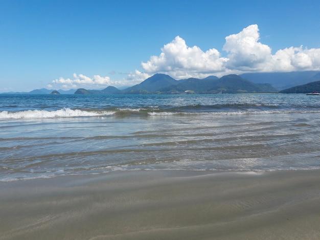 Landschap met strand, zee, bergen en wolken in de lucht.