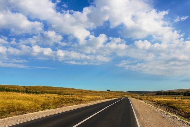 Landschap met uitzicht op de weg die door velden en heuvels leidt