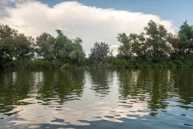 Landschap met waterlijn, riet en vegetatie, waterweerspiegelingen, in de donaudelta