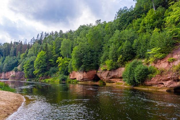 Landschap met zandstenen kliffen op de oever van de gauja, snel stromend en helder rivierwater, kuku kliffen, gauja national park, letland