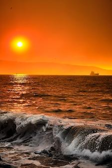 Landschap met zonsondergang en gigantische golven aan de kust. silhouet van vogels en boot op het water op een gouden uurzonsondergang