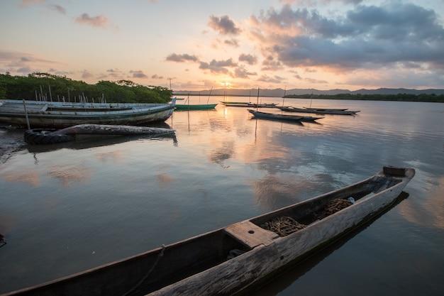 Landschap met zonsondergang met visserskano's aan de rivierrand.