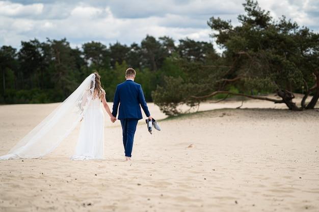 Landschap shot van een paar wandelen op zand op hun trouwdag