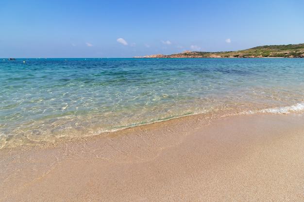 Landschap shot van een zandstrand in een zonnige heldere blauwe hemel
