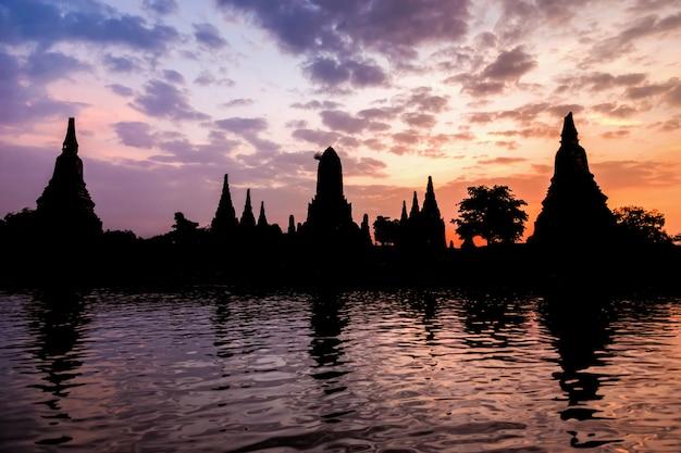 Landschap silhouet van wat chaiwatthanaram tijdens zonsondergang naast de chao phraya-rivier is oude tempel beroemde religieuze attractie van ayutthaya historical park, thailand