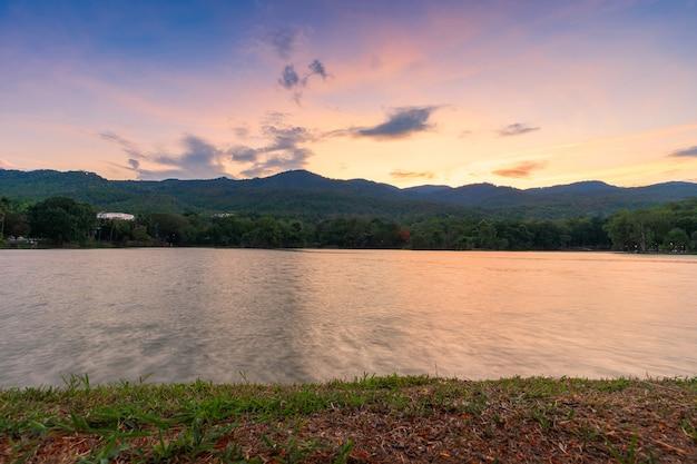 Landschap uitzicht op het meer op ang kaew chiang mai university in natuur bos uitzicht op de bergen met avond blauwe dramatische avondrood achtergrond