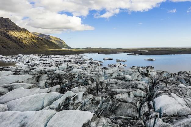 Landschap van badlands bedekt met ijs omgeven door water onder het zonlicht