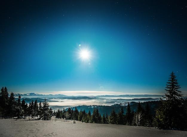 Landschap van besneeuwde skihelling op de achtergrond van sparrenbossen en bergketens in het maanlicht