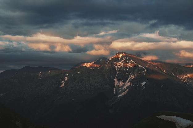 Landschap van de berg het piekzonsondergang met sombere dramatische hoofdzakelijk bewolkte hemel en oranje en rode zonstralen