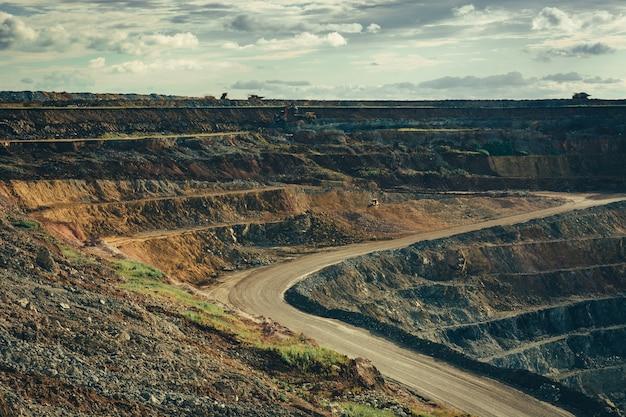 Landschap van de diepe steengroeve met werkende machines. extractie van grondstoffen. Premium Foto