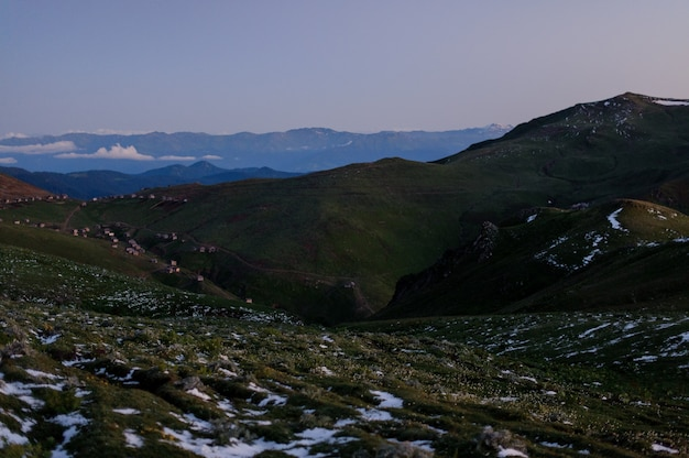 Landschap van de heuvels bedekt met sneeuwresten en huizen op de achtergrond van de avondhemel