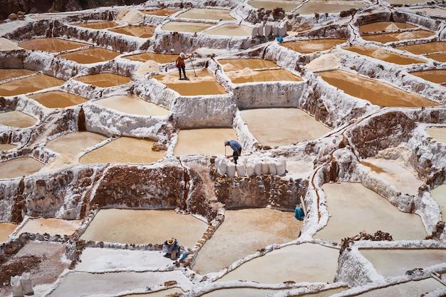 Landschap van de maras-zoutmijnen en hun arbeiders in de regio cusco, peru, heilige vallei