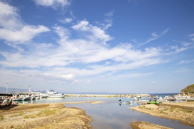 Landschap van de zee met boten erop omgeven door heuvels onder een blauwe hemel