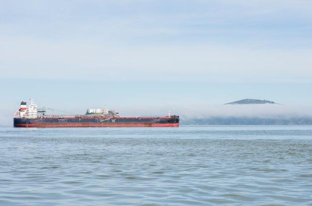 Landschap van de zee met een boot en het eiland alcatraz doorboord door mist
