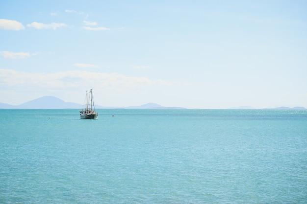 Landschap van de zee met een schip erop onder een blauwe lucht en zonlicht