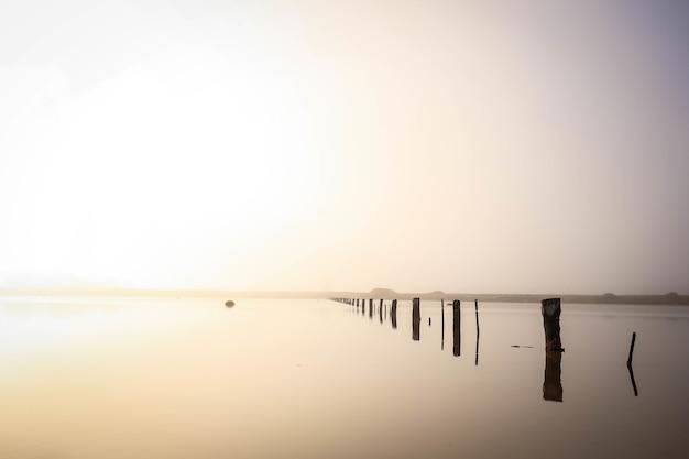 Landschap van de zee met houten planken van een onafgewerkt dok erin onder het zonlicht
