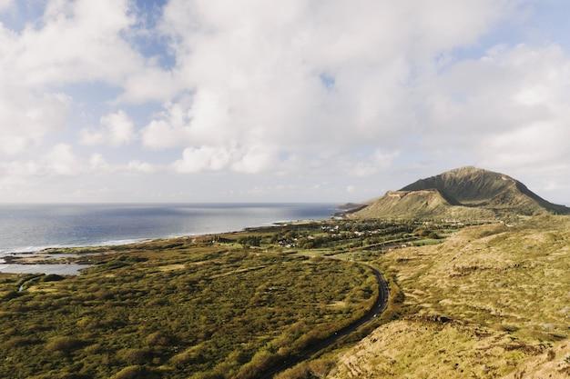 Landschap van de zee omgeven door groen onder een bewolkte hemel en zonlicht