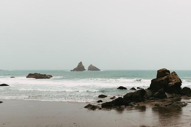 Landschap van de zee, omringd door rotsen en strand onder een bewolkte hemel overdag