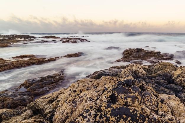 Landschap van de zeekust met water tussen de rotsen, golven die tegen de rotsen slaan en reflecties van de lucht. gran canaria. spanje europa,