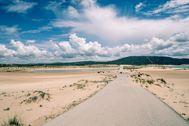 Landschap van een lege weg, enkele heuvels aan de horizon en pluizige wolken aan de hemel