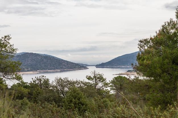 Landschap van een meer omgeven door bomen en bergen