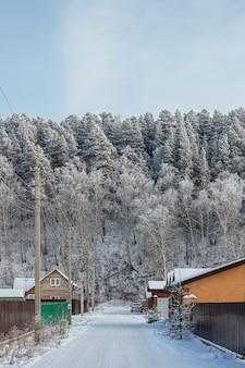Landschap van een mooi klein dorpje met houten huizen, weg, auto. prachtig magisch bos en stad