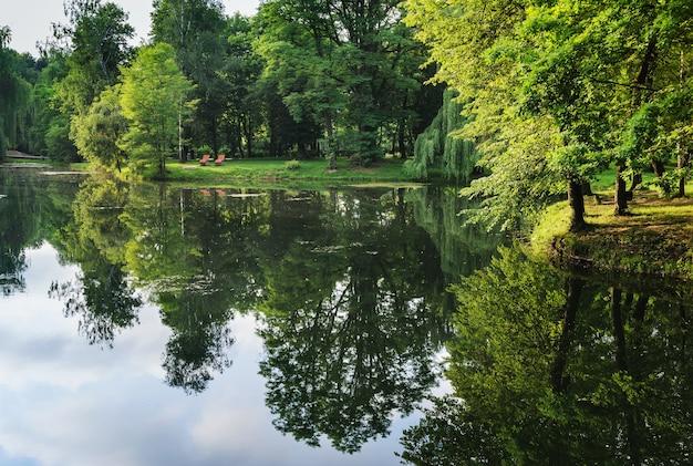 Landschap van een stadspark. een meer weerspiegelt de bomen en wolken. op een tegenoverliggende oever staan twee houten ligbedden.