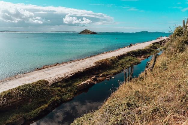 Landschap van een strand in rio de janeiro met een zandweg en bergformatie