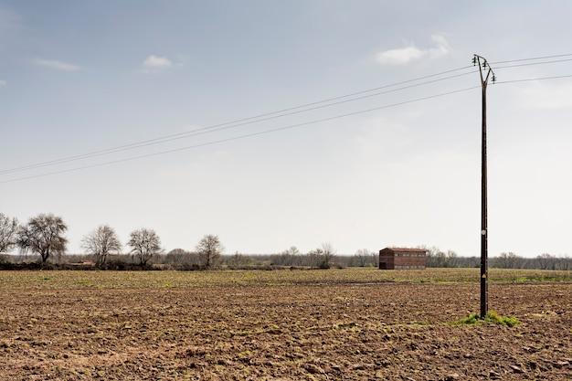 Landschap van een tabaksteeltveld met een elektriciteitstorentje en een tabaksdroger op de achtergrond, landbouw