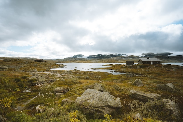 Landschap van een veld omgeven door groen en hutten onder een bewolkte hemel in finse, noorwegen