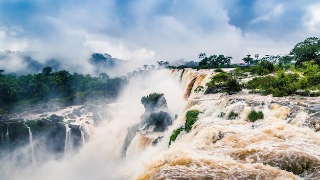 Landschap van een waterval omgeven door bossen bedekt met mist onder een bewolkte hemel