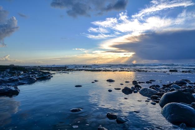 Landschap van een zee bedekt met rotsen onder het zonlicht en een bewolkte hemel tijdens de zonsondergang