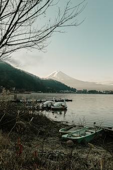 Landschap van fuji-bergmening en kawaguchiko-meer met boten in ochtendzonsopgang, wintertijden in yamanachi, japan.
