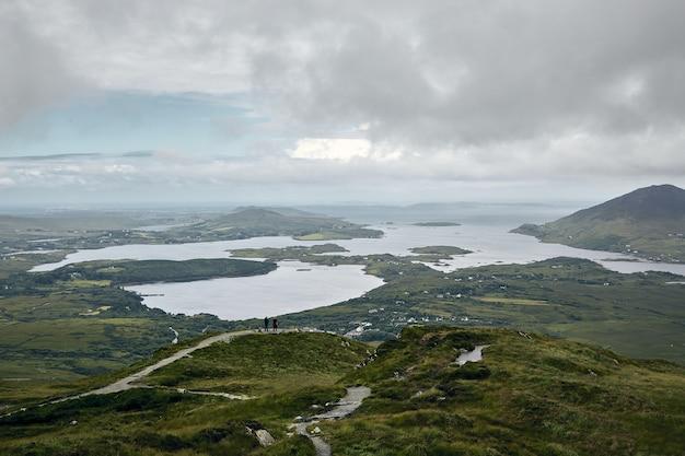 Landschap van het connemara national park, omringd door de zee onder een bewolkte hemel in ierland