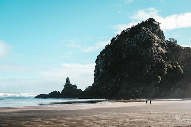 Landschap van het piha-strand en hoge rotsen met de mensen die er onder een blauwe lucht omheen lopen